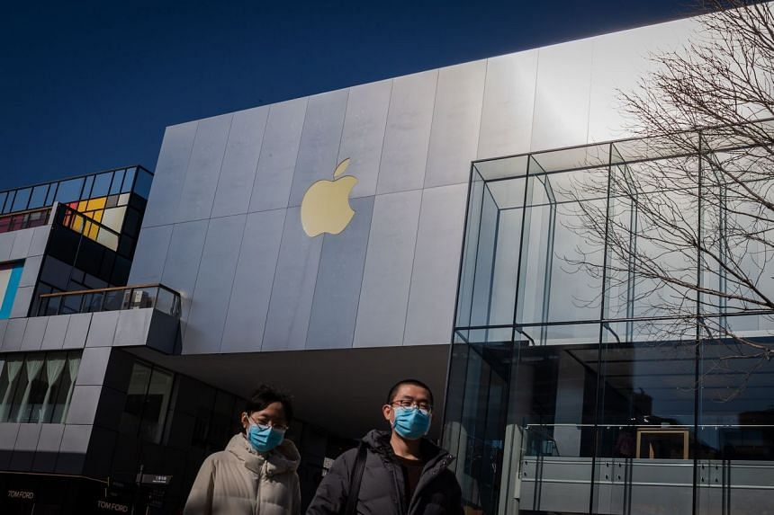A couple wearing facemasks to protect against the coronavirus walk outside an Apple Store in Beijing on Feb 22, 2020.