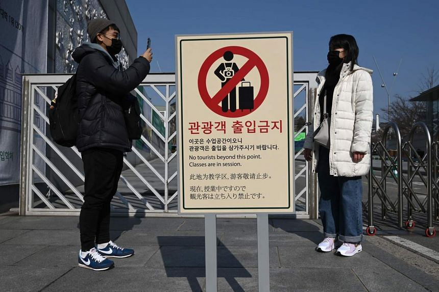 """People wearing face masks take a photo next to a """"no tourists"""" sign at the main entrance of a university in Seoul on Feb 4, 2020."""