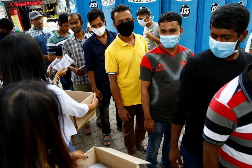 Migrant workers mostly from Bangladesh queue to collect free masks and have their temperatures checked in Singapore on Feb 23, 2020.