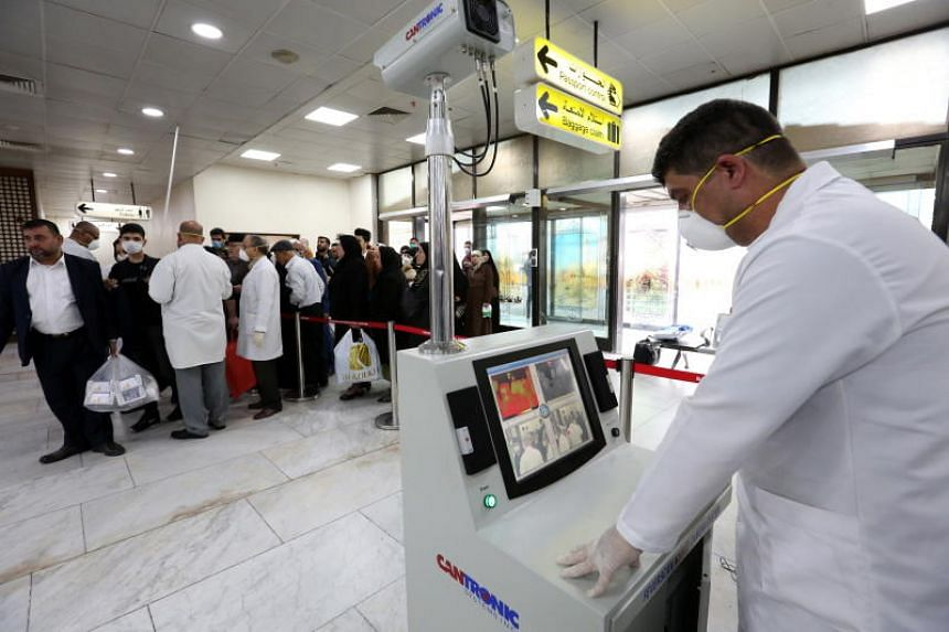 Members of Iraqi medical team check passengers upon arrival from Iran at Baghdad international airport in Baghdad, Iraq, on Feb 24, 2020.