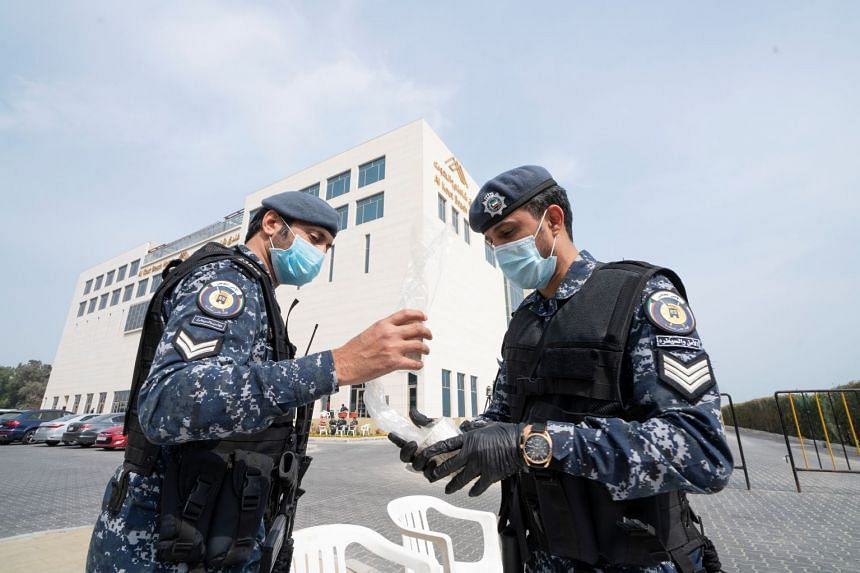 Kuwaiti special forces officers wearing protective masks are seen at the entrance to a hotel where people evacuated from Iran are being held in quarantine, in Fahaheel, Kuwait.