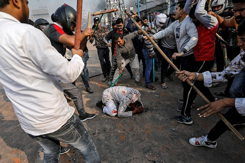 Above: A widely shared photo of a bloodied man on the ground surrounded by attackers in New Delhi on Monday. Left: Men pelting stones and starting fires during clashes in eastern Delhi between groups for and against India's Citizenship Amendment Act.