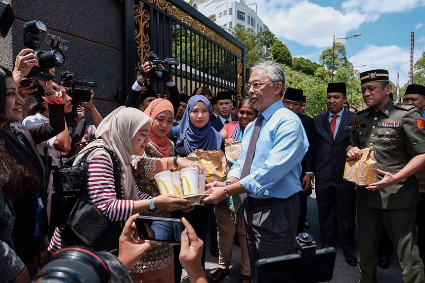 Malaysia's King Abdullah Ri'ayatuddin handing out packages of fast food to reporters standing outside the National Palace in Kuala Lumpur on Feb 25, 2020.