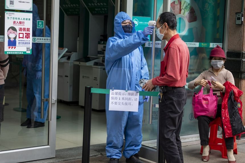 A security guard with a mask and protective gear takes a visitor's temperature at the entrance to a bank in Guangzhou on Feb 24, 2020.