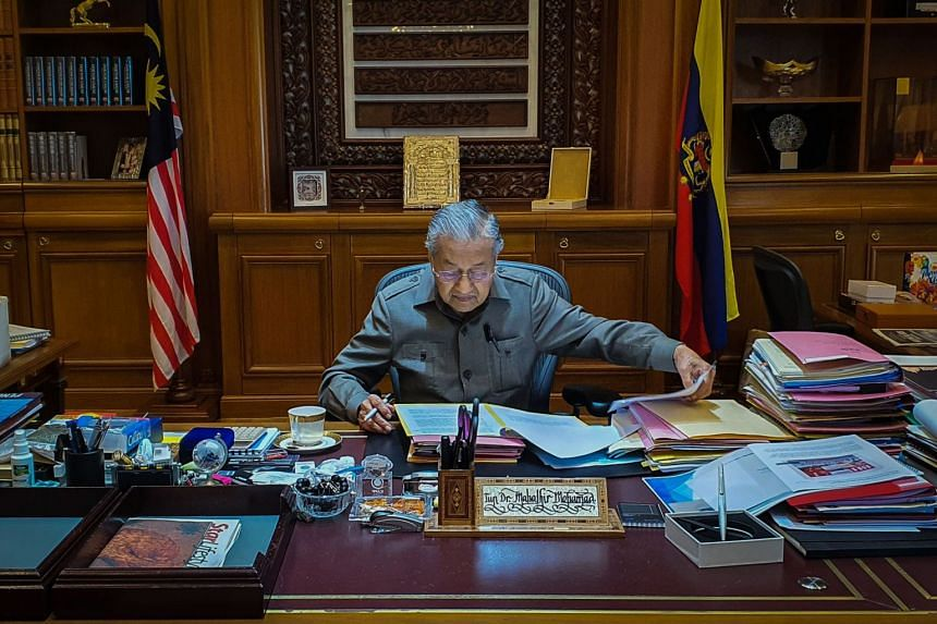 A photo taken on Feb 25, 2020, shows shows interim prime minister Mahathir Mohamad working in his office in Putrajaya.