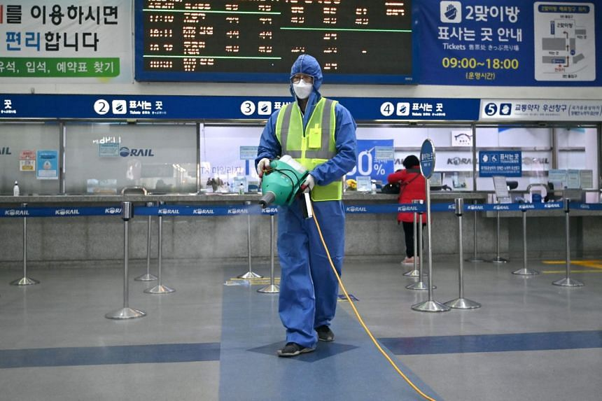 A worker wearing protective gear sprays disinfectant as part of preventive measures against the spread of the coronavirus, at a railway station in Daegu on Feb 26, 2020.