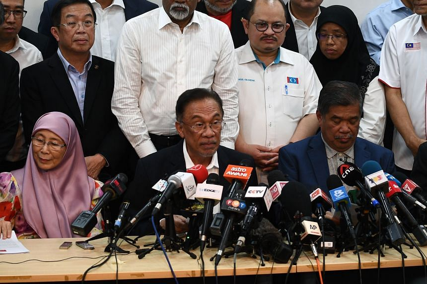 Datuk Seri Anwar Ibrahim (centre) during a press conference at the People's Justice Party headquarters in Petaling Jaya on Feb 26, 2020. Next to him is his wife Wan Azizah Wan Ismail and Malaysian Defence Minister Mat Sabu.