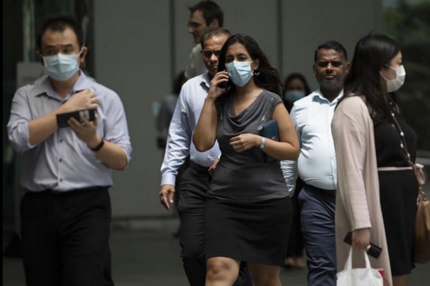 People wearing masks walk around the Central Business District (CBD) in Singapore on Feb 12, 2020.