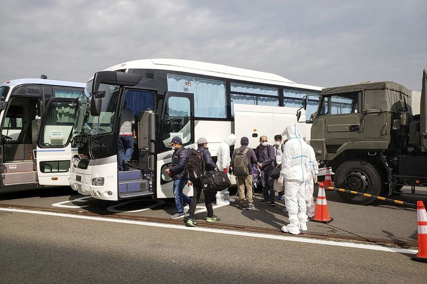 Officials from the Philippine Embassy and Department of Health boarding a bus with Filipinos from the Diamond Princess cruise ship in Yokohama, Japan, on Feb 25, 2020.