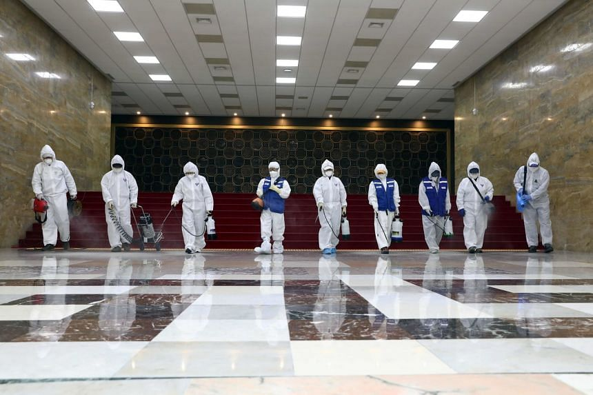 Workers spray disinfectant as part of preventive measures against the spread of the coronavirus at the National Assembly in Seoul, on Feb 25, 2020.