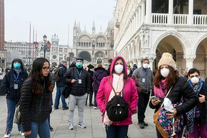 A photo taken on Feb 25, 2020, shows tourists with protective masks in Venice.