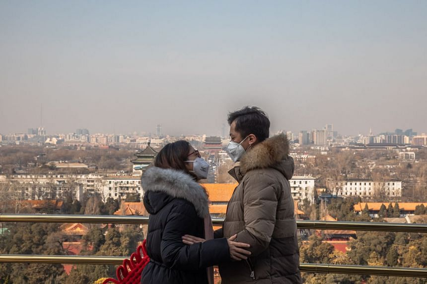 A couple wearing protective face masks embrace at a viewing area of Jingshan Park in Beijing, on Feb 23, 2020.