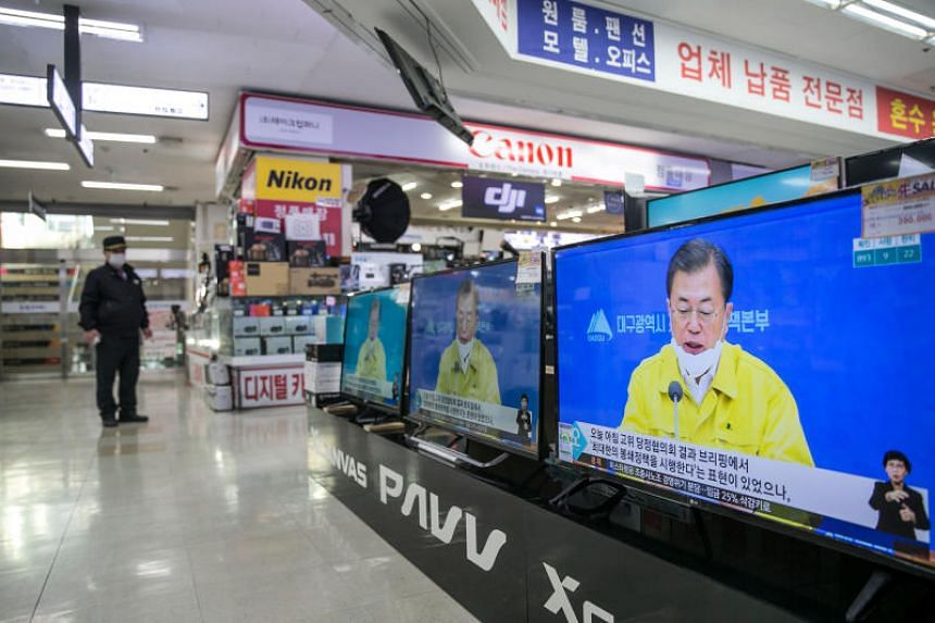 A security guard with a mask stands in front of the electronics shop in Seoul, on Feb 25, 2020, as South Korean President Moon Jae-in appears on TV.