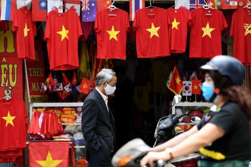 A man wearing a protective face mask walks past a souvenir shop in Hanoi, Vietnam, on Feb 26, 2020.