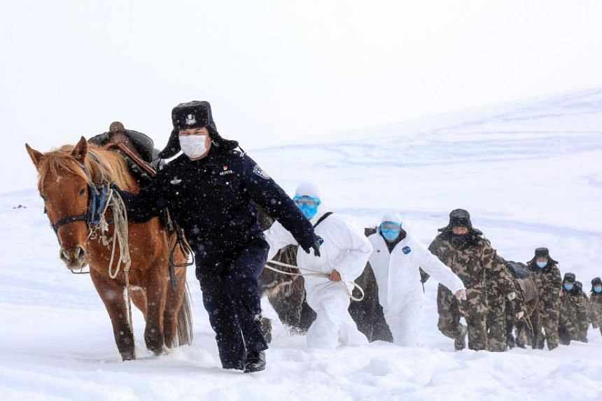 Police officers wearing protective face masks walking with horses on their way to visit residents who live in remote areas in Xinjiang, China, on Feb 19, 2020.