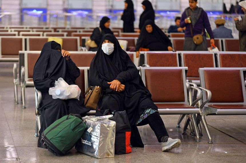 Iraqis returning from Iran wear protective masks upon their arrival at the Najaf International Airport on Feb 21, 2020.