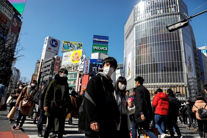 People wearing protective masks in the Shibuya shopping district in Tokyo, Japan, on Feb 24, 2020.