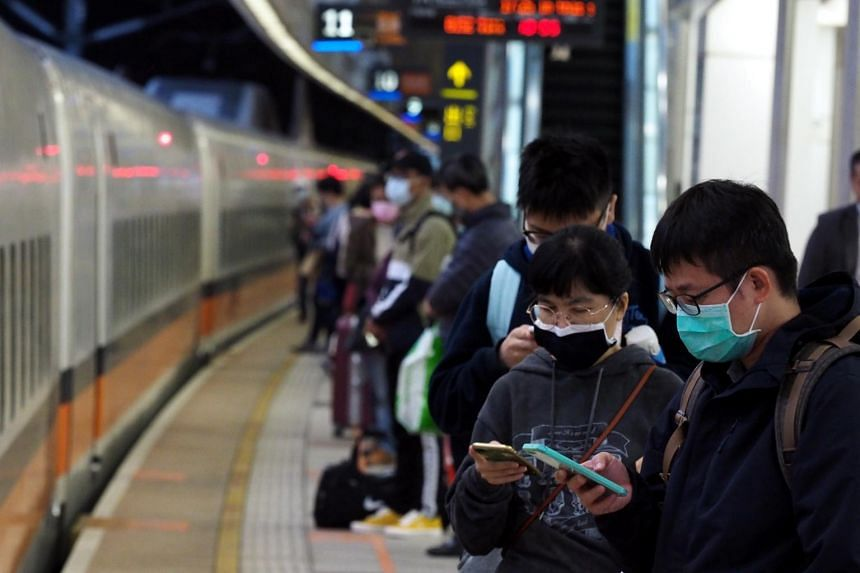 Passengers wearing face masks wait to board a high-speed train in Kaohsiung, Taiwan, on Feb 23, 2020.