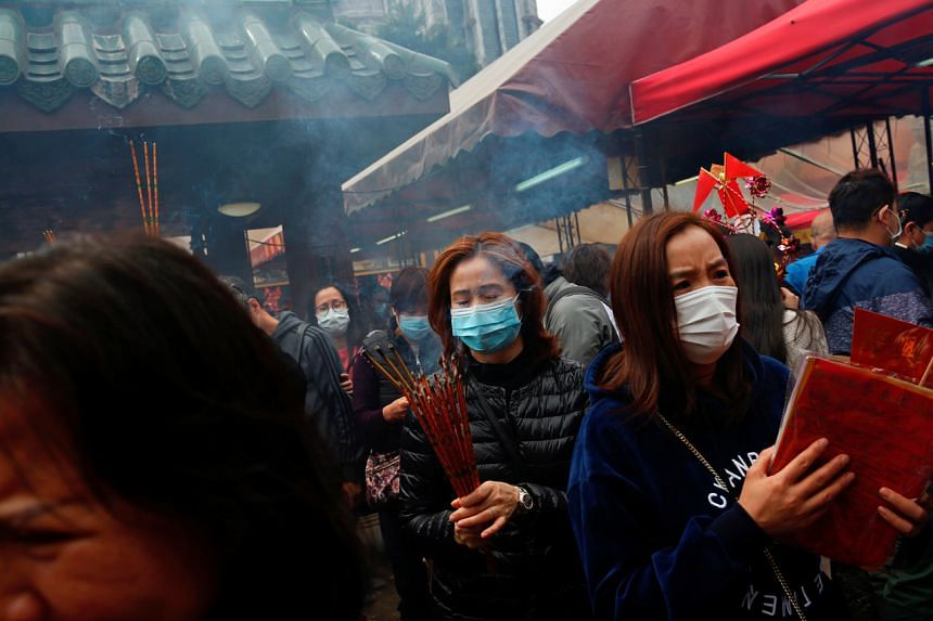 In a photo taken on Jan 26, 2020, worshippers wear masks as they make offerings of incense sticks during a Chinese New Year celebration at a temple in Hong Kong.