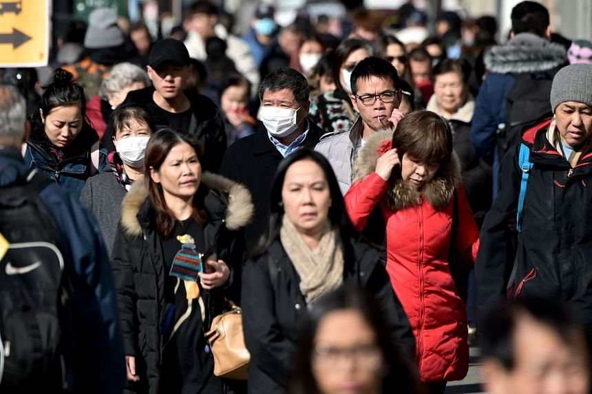 People wear surgical masks in fear of the coronavirus in Flushing, a neighborhood in the New York City borough of Queens, on Feb 3, 2020.