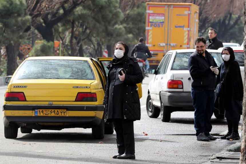 Iranians wearing protective face masks wait for taxis on a street of Teheran, Iran, on Feb 26, 2020.