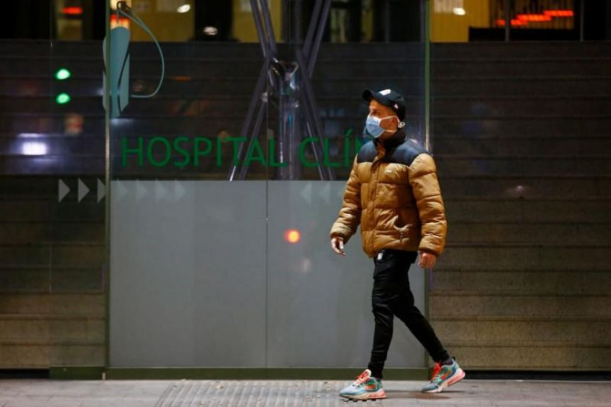 A man wearing a protective mask walks outside the Hospital Clinic in Barcelona, Spain, on Feb 25, 2020.