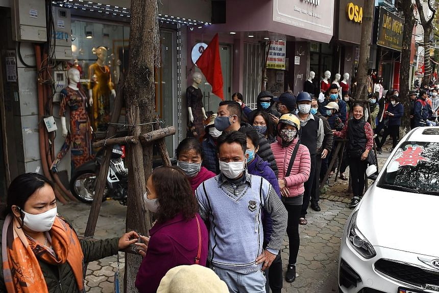 Face masks are flying off the shelves in many countries. There were long queues to buy masks last week in Hanoi, Vietnam (above, left), and people scrambled to buy them in the Philippines (above, right) after the government confirmed the country's fi