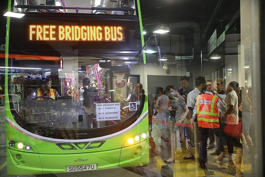 Commuters queueing (top and above) for the bridging bus service at Sengkang Bus Interchange. They took the free service to Buangkok MRT station to continue their journey on the North East Line. ST PHOTOS: ONG WEE JIN