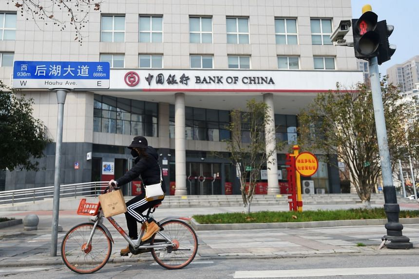 A woman wearing a face mask rides a bicycle past a Bank of China branch in Wuhan, on Feb 25, 2020.