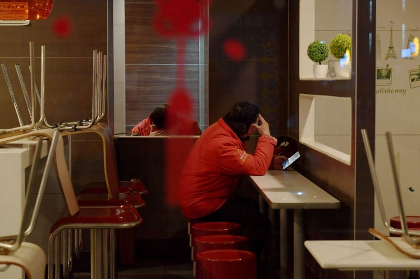 Delivery workers wait for orders in a McDonald's restaurant in Nanjing, Jiangsu province, on Feb 17, 2020.
