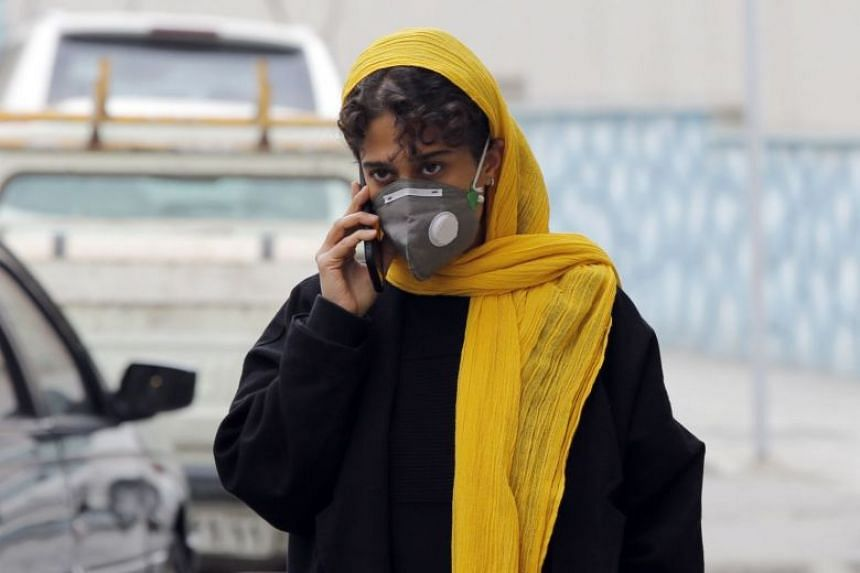 An Iranian woman is seen wearing a face mask in Teheran, Iran, on Feb 24, 2020. Our Asian Insider podcast discusses the coronavirus outbreak in Iran and its impact on the Middle East.