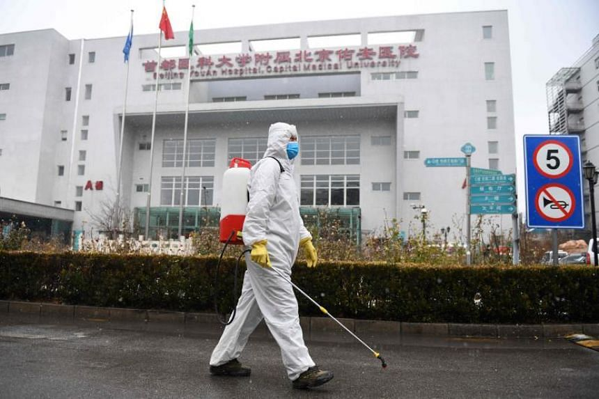 A worker sterilises a path at the Youan Hospital in Beijing on Feb 14, 2020. The hospital is one of twenty hospitals in Beijing treating coronavirus patients.