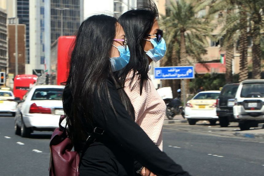 People wear protective masks in Kuwait City on Feb 27, 2020.