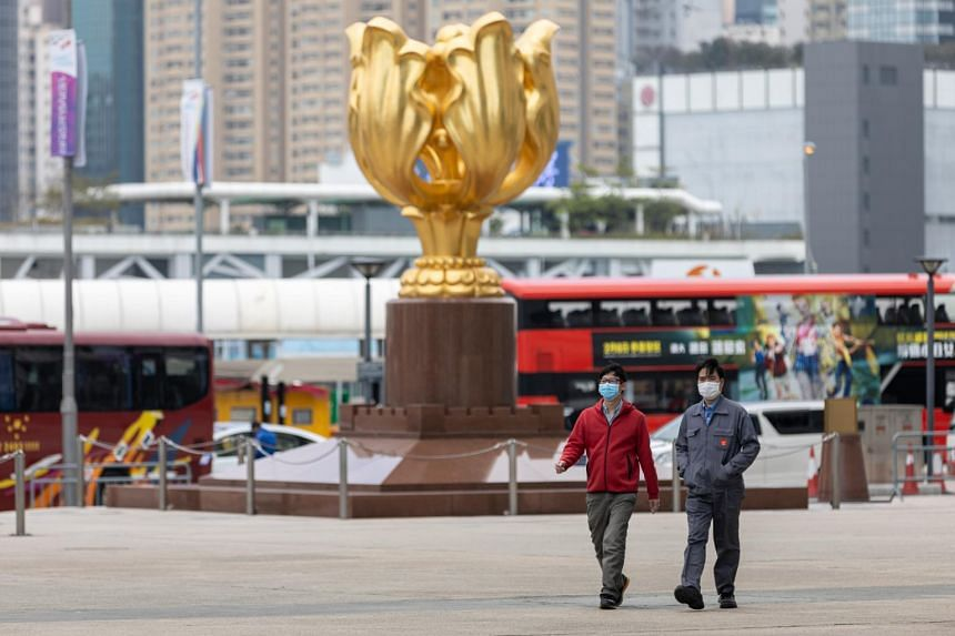 Men wearing masks walk past the Golden Bauhinia statue in Bauhinia Square, Hong Kong, on Feb 24, 2020.