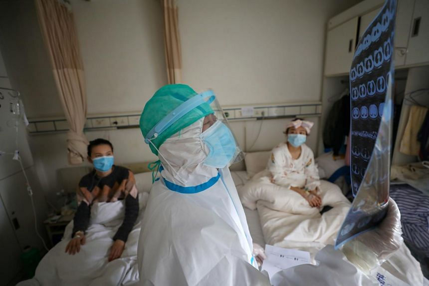 A medical worker in protective suit inspects a CT scan image at a ward of Wuhan Red Cross Hospital in Wuhan, China, on Feb 24, 2020.