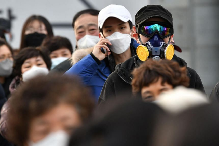 A man wears a mask and goggles as he waits in line to buy face masks from a post office near the Daegu branch of the Shincheonji Church of Jesus in Daegu on Feb 27, 2020.