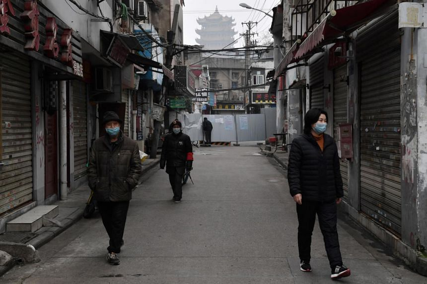 People wearing masks are seen in an alley near the Yellow Crane Tower in Wuhan, the epicentre of the novel coronavirus outbreak, Hubei province, China, on Feb 27, 2020.
