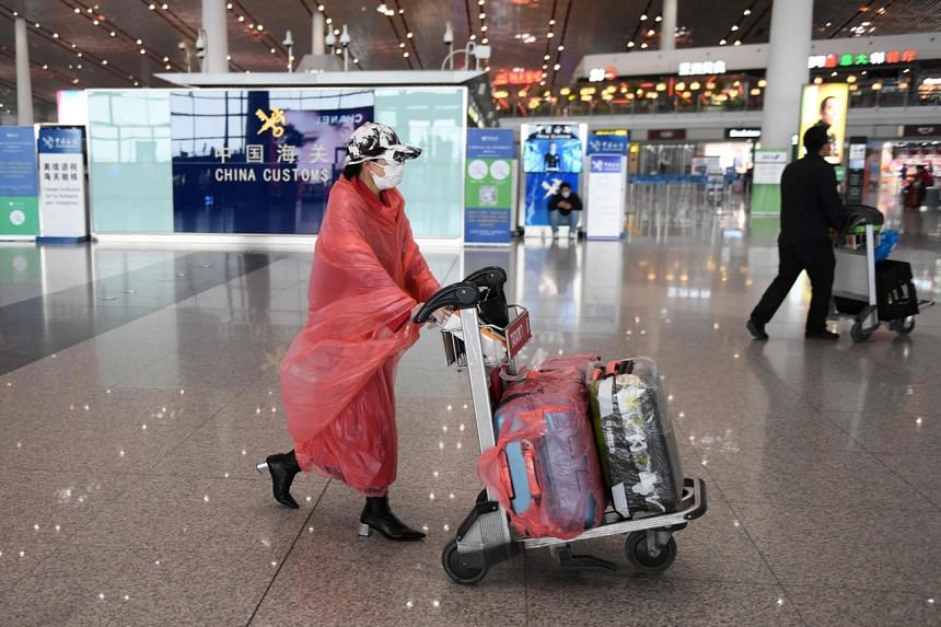 A woman wears protective clothing as she walks through Beijing Capital Airport on Feb 24, 2020.