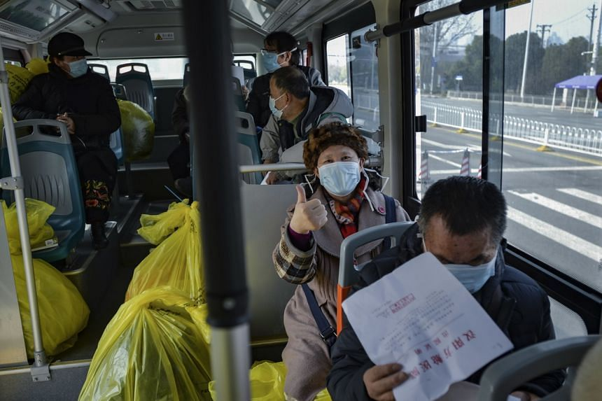A photo taken on Feb 22, 2020, shows recovered Covid-19 patients, just discharged from a temporary hospital, riding a designated bus to another quarantine facility in Wuhan, China.