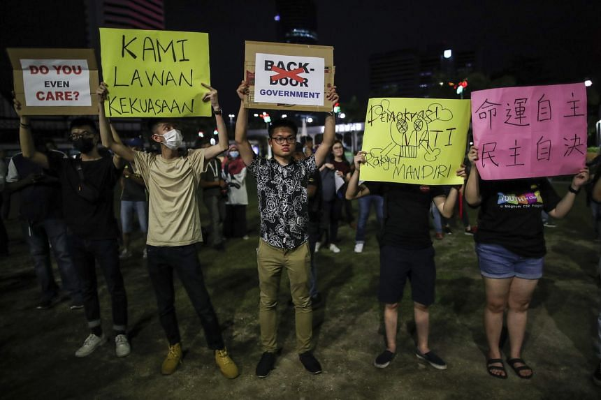 Protesters hold placards during a demonstration at Independence Square in Kuala Lumpur, on Feb 25, 2020.