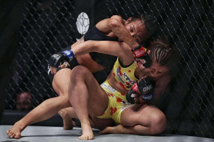 Tiffany Teo of Singapore punching Ayaka Miura of Japan during their strawweight bout in One Championship's King of the Jungle event at the Singapore Indoor Stadium on Feb 28, 2020.