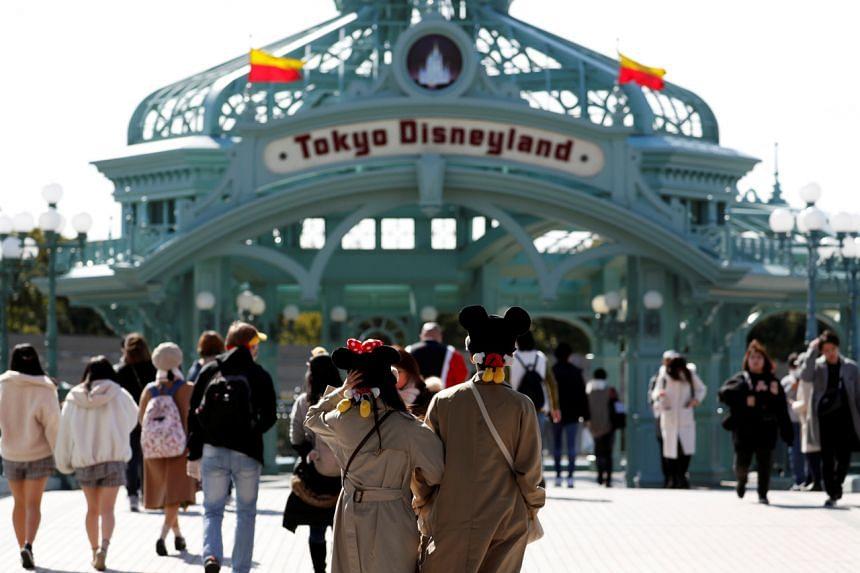 Visitors are seen outside Tokyo Disneyland in Urayasu, east of Tokyo, Japan, on Feb 28, 2020.