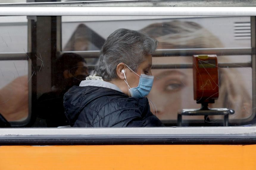 A woman wearing a protective mask travels on a public tram in Milan, Italy.