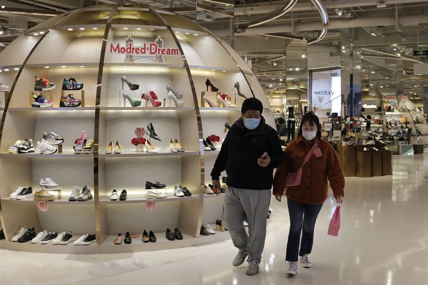 People wearing protective masks shop at a mall in Beijing, China, Feb 28, 2020.
