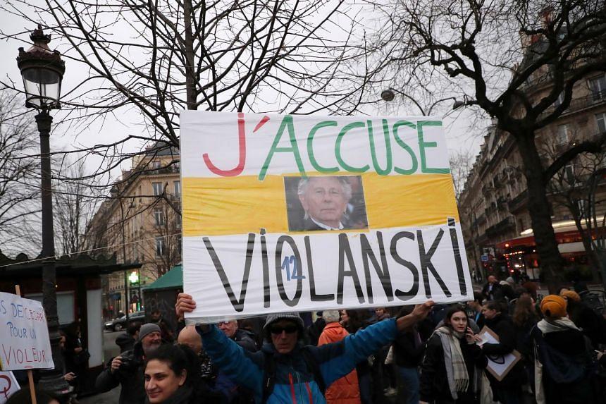 "A protester holds a sign reading ""J'accuse Violanski"" (I accuse Rape-anski) in Paris,  Feb 28 2020."
