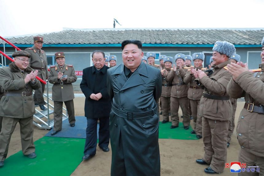 A November 2019 photo shows Kim (centre) overseeing a super-large multiple launch rocket system test.