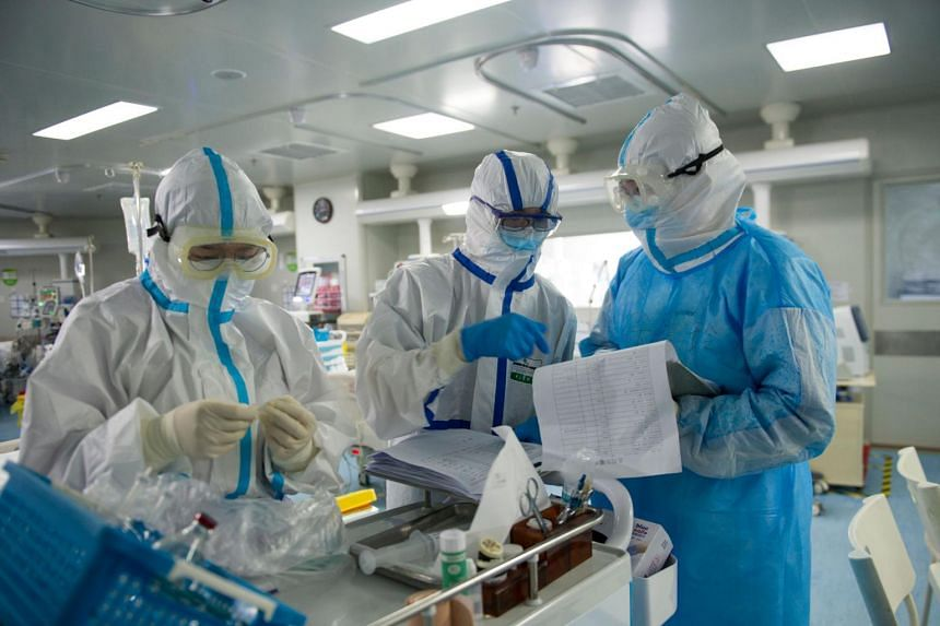 A photo taken on Feb 22, 2020 shows medical staff checking notes in an intensive care unit treating Covid-19 patients at a hospital in Wuhan.