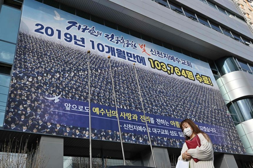 A woman with a face mask walks in front of the Daegu branch of the Shincheonji Church of Jesus, on Feb 27, 2020.