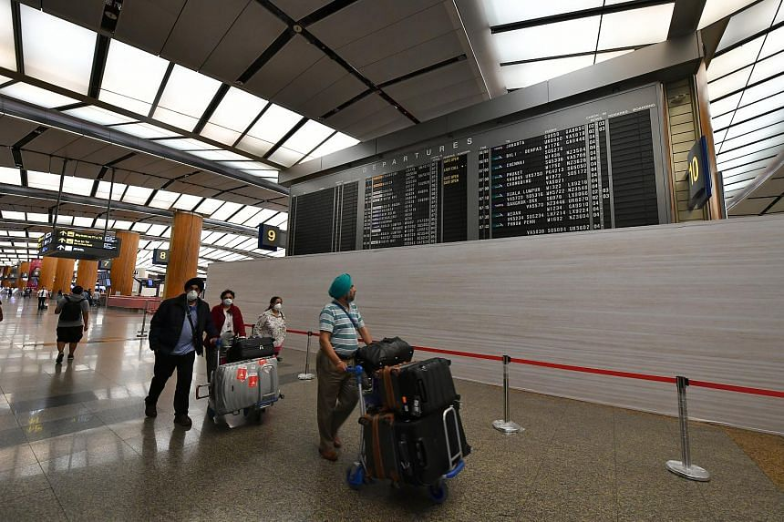 Travellers walking past one of Changi Airport Terminal 2's analogue flight information display flip board, minutes before its decommissioning at 11.30pm, on Feb 6, 2020.