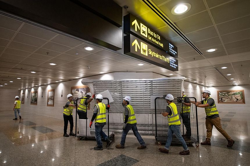 Contractors transporting one of the pieces of the analogue flight information display flip board's holding structure for loading onto a truck, at Changi Airport Terminal 2 after midnight on Feb 27, 2020.